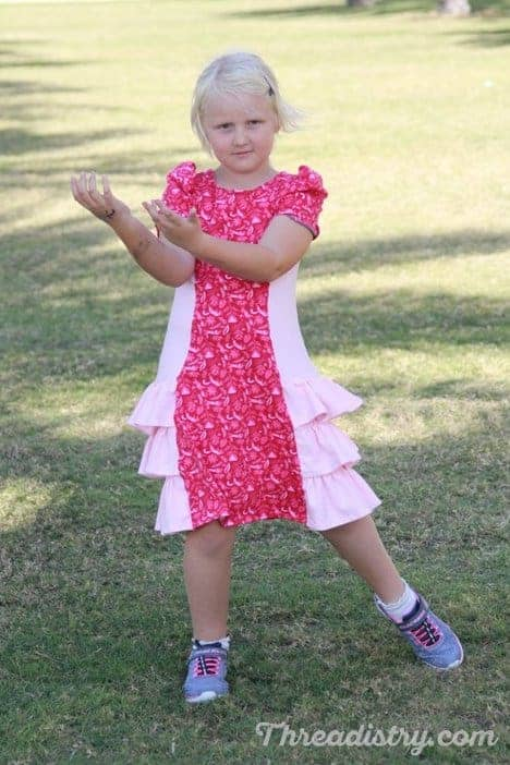 Girls dress sewing pattern from Ellie and Mac with ruffles and gathered short sleeves.