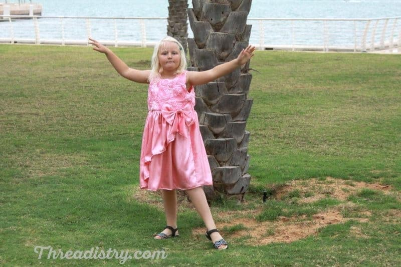Little girl wearing the Poinsettia Party Dress by GYCT Designs
