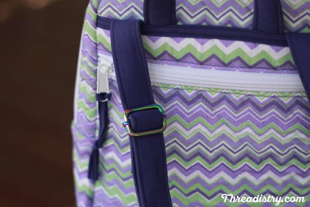 Iridescent rainbow bag hardware on backpack straps.