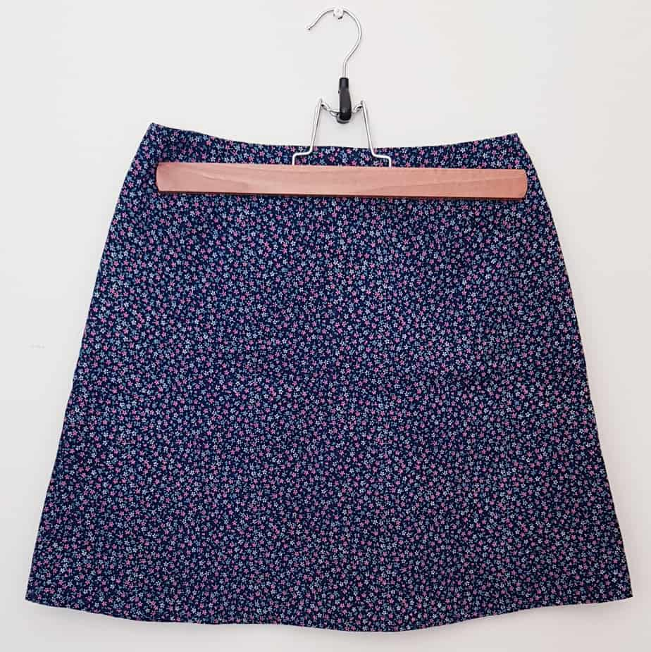 A-line short skirt in navy blue print with small pink flowers, hanging on a coat hanger