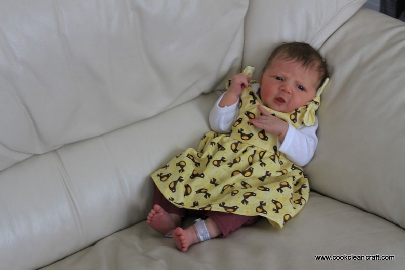 Newborn baby on sofa wearing yellow dress with birds