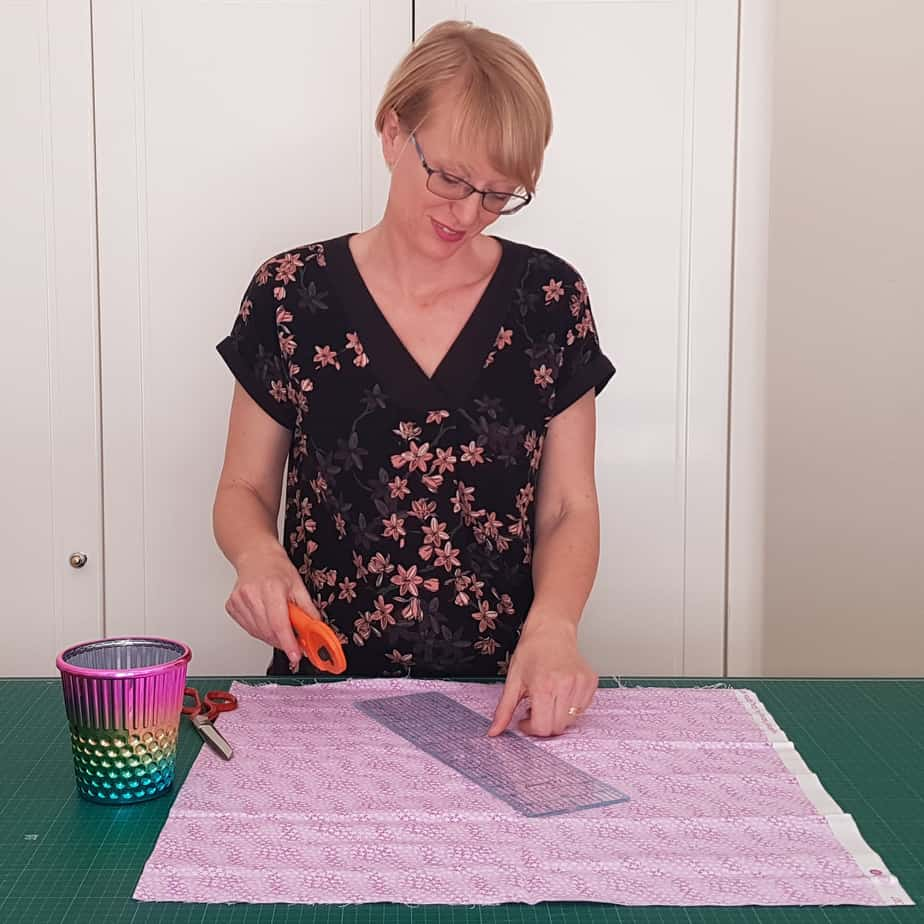 Threadistry creator Narelle standing at table cutting fabric