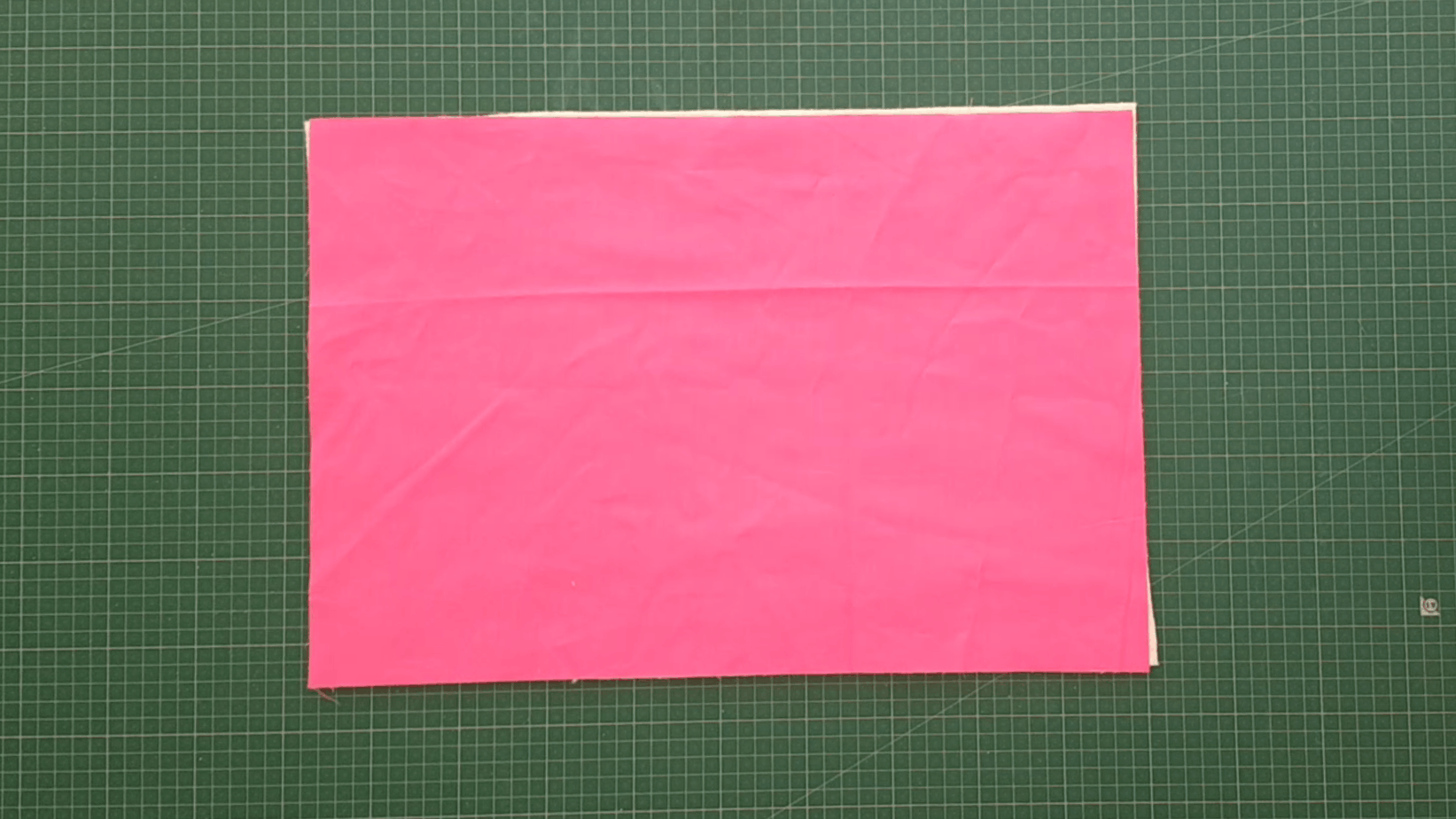 """13"""" x 19"""" rectangle of pink fabric lying on top of the same size quilt batting on a cutting mat."""