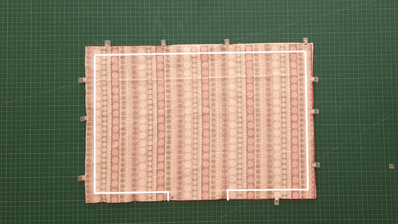 Placemat fabric with line drawn for how to sew the layers together and leave an opening.