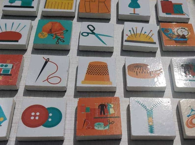 Felt-backed marble tiles with sewing pictures on top, to be used as sewing pattern weights.