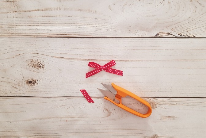 Scissors trimming the tail of a perfect ribbon bow