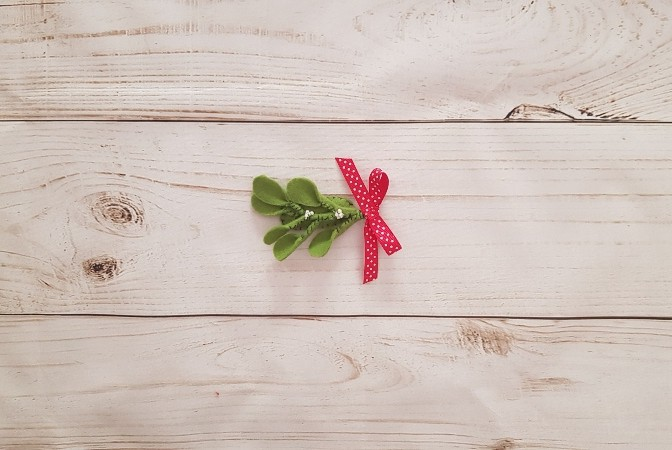 Completed DIY felt mistletoe hairclip with red ribbon bow