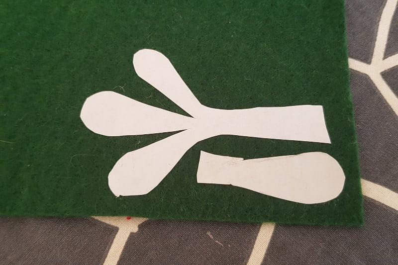 Felt mistletoe template in freezer paper stuck to green felt