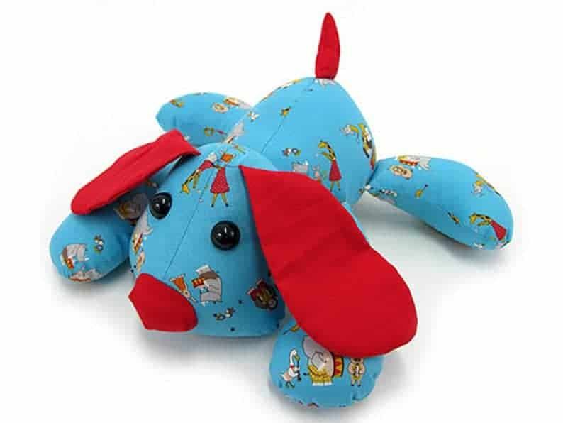 Fabric stuffed dog with red ears, nose and tail