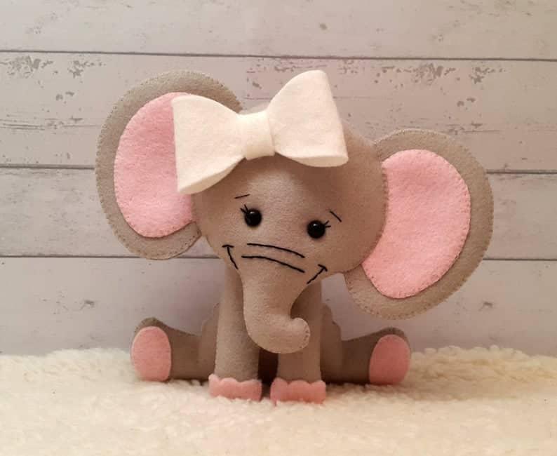 Cute felt elephant sitting down with big bow on her head