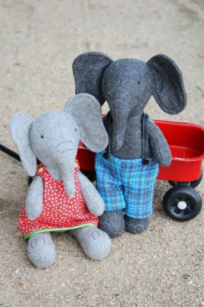 Two stuffed elephant dolls - one wearing a dress and one wearing overalls.